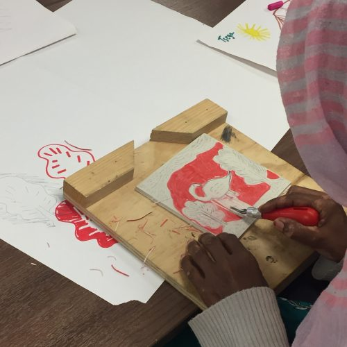Participants carving and printing linocuts, based on imagery from a storytelling component of the project.